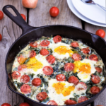 Easy one-dish kale-stuffed skillet starts on the stovetop with a big handful of cherry tomatoes, then slides into the oven to bake egg yolks to gooey, salty perfection.