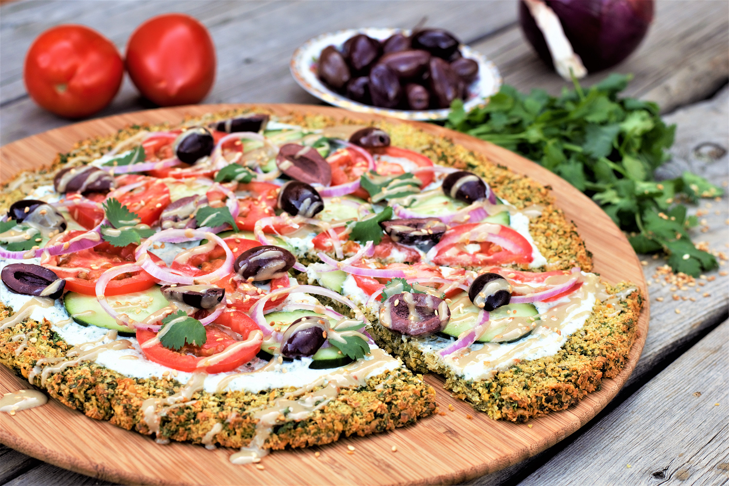 Everyone's favorite Middle Eastern sandwich on a pizza! Crunchy, bright, fresh veggies over creamy tzatziki on a crispy golden falafel crust is healthy eating at its very best: high protein & fiber, low carb, gluten free, vegetarian, zero added sugar, and downright delicious all around.