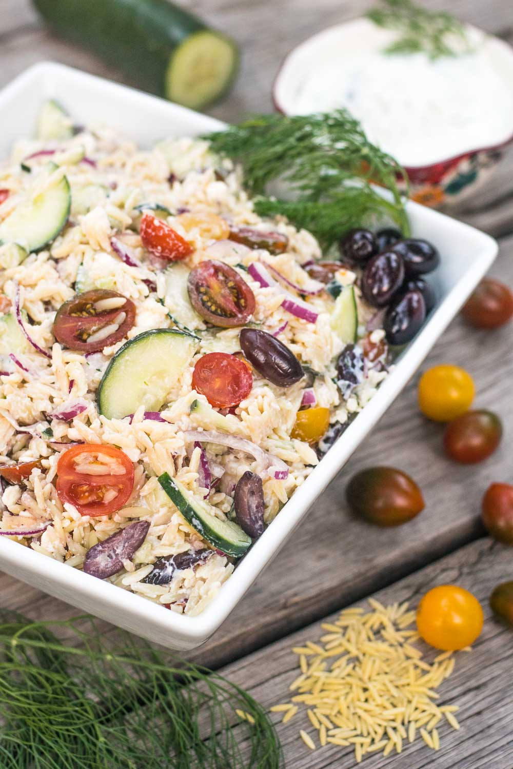 Greek-inspired pasta salad starring homemade tzatziki - aka delicious tangy yogurt sauce - that's loaded with fresh veggies and perfect for picnics!